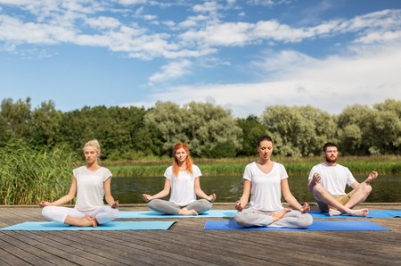 fitness, sport, yoga and healthy lifestyle concept - group of people meditating in lotus pose on river or lake berth Imagens