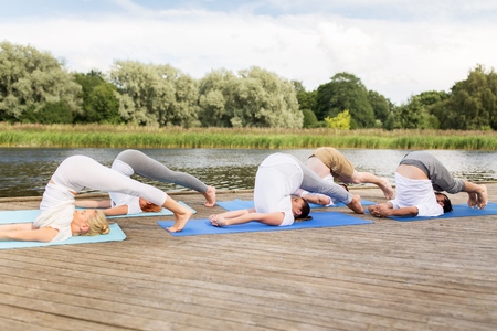 middle class: fitness, sport, yoga and healthy lifestyle concept - group of people making plow pose on mat outdoors on river or lake berth Stock Photo