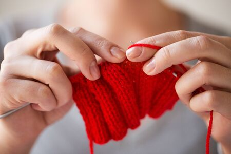 people and needlework concept - close up of woman hands knitting with needles and red yarn Stock Photo