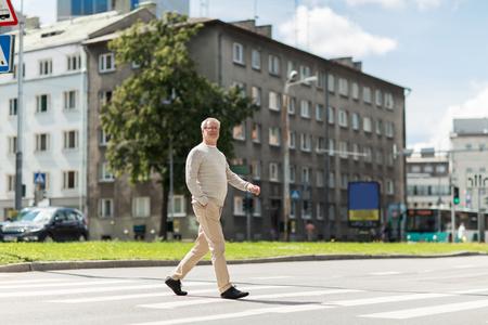 pedestrian crossing: leisure and people concept - senior man walking along summer city crosswalk