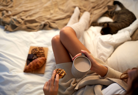 aroma: winter, coziness, leisure and people concept - close up of young woman with cup of coffee or cacao and cookie in bed at home