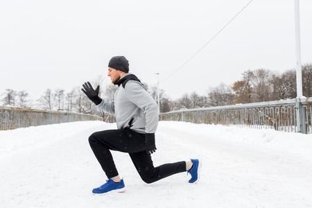 fitness, sport, people, exercising and healthy lifestyle concept - young man doing squats and warming up on snow covered winter bridge