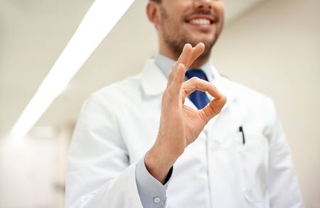 healthcare, gesture, people and medicine concept - close up of happy male doctor at hospital showing ok hand sign