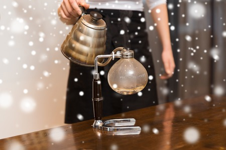 siphon: equipment, coffee shop, people and technology concept - close up of woman with pot pouring hot water to coffeemaker filter at cafe bar or restaurant kitchen over snow Stock Photo