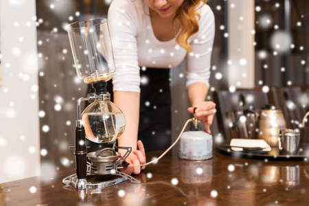 siphon: equipment, coffee shop, people and technology concept - close up of woman with butane gas burner heating water in siphon coffeemaker at cafe bar or restaurant kitchen over snow