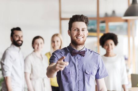 finger bow: business, startup, people, gesture and teamwork concept - happy young man with beard and bow tie pointing finger at you over creative team in office