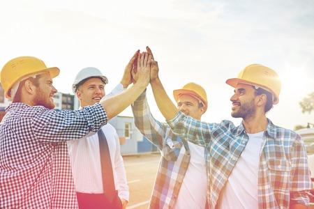 het bedrijfsleven, de bouw, partnership, gebaar en mensen concept - close-up van lachende bouwers en architect in bouwvakkers het maken van high five in openlucht Stockfoto