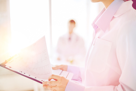 beating: healthcare and medicine concept - close up of female holding clipboard with cardiogram