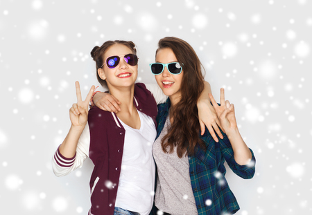 female christmas: winter, christmas, people, fashion and gesture concept - happy smiling pretty teenage girls or friends in sunglasses showing peace hand sign over gray background and snow