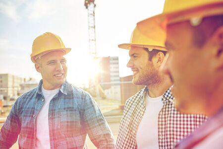 het bedrijfsleven, de bouw, teamwork en mensen concept - groep lachende bouwers in bouwvakkers op de bouwplaats
