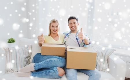 in movimento, la gente, la riparazione e immobiliari concetto - coppia felice con le grandi scatole di cartone che mostra il pollice in alto sul divano a casa nuova sulla neve