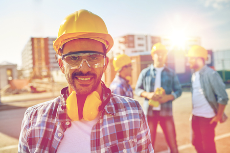residential area: business, building, teamwork and people concept - smiling builder with hardhat and headphones over group of smiling builders at construction site