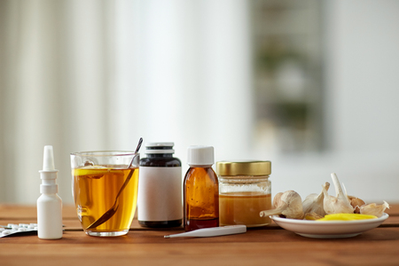 healthcare, traditional medicine and flu concept - drugs, thermometer, honey and cup of tea on wooden table Stock Photo