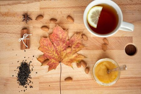 autumn and ethnoscience concept - cup of lemon tea and honey on wooden board with maple leaf and almond