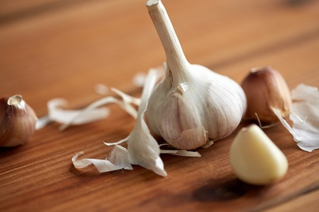 indigenous medicine: health, food, cooking, traditional medicine and ethnoscience concept - close up of garlic on wooden table