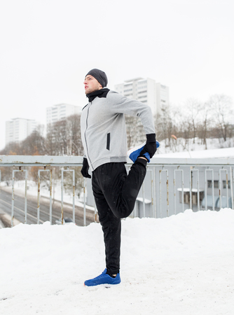 fitness, sport, people, exercising and healthy lifestyle concept - young man stretching leg and warmig up on snow covered winter bridge Stock Photo
