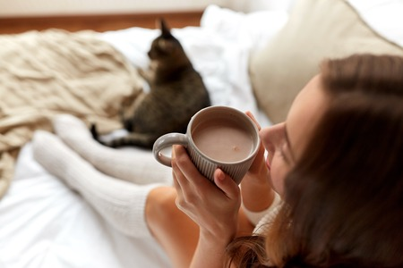 coziness: winter, coziness, leisure and people concept - close up of happy young woman with cup of coffee or cacao and cat in bed at home