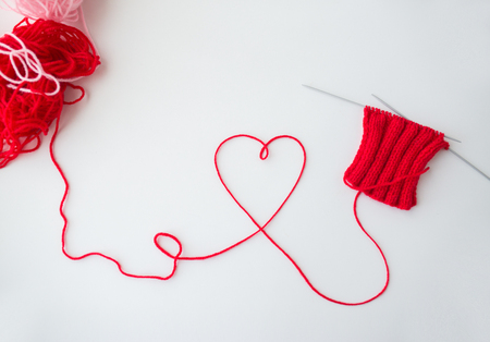 handicraft, love, valentines day and needlework concept - hand-knitted item with knitting needles and thread in heart shape Stock Photo