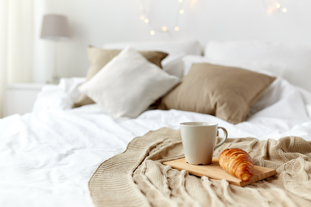 coziness: breakfast, coziness, morning, holidays and winter concept - cozy bedroom with coffee cup and croissant on wooden board in bed at home