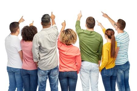 多様性、競争、民族性および人々 のコンセプト - 幸せな笑みを浮かべて男性と白で何かに指を指す女性の国際的なグループ 写真素材