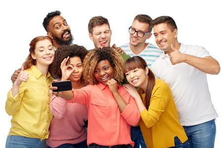 la diversité, la race, l'origine ethnique, la technologie et les gens concept - groupe international d'hommes et de femmes heureuses sourire prenant selfie par téléphone intelligent sur blanc Banque d'images