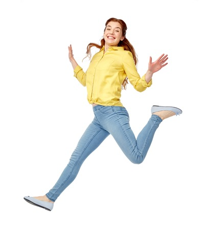 happiness, freedom, motion and people concept - smiling young woman jumping in air