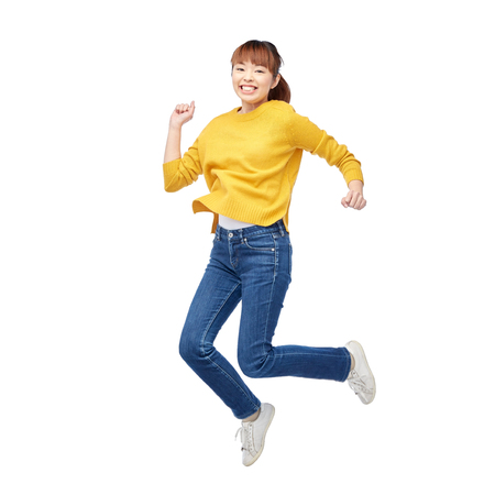 happy asian people: people, motion and action concept - happy asian young woman jumping over white