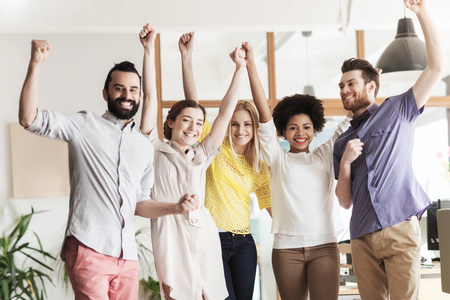 personas celebrando: business, triumph, gesture, people and teamwork concept - happy international creative team raising hands up and celebrating victory in office
