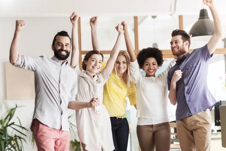 negocio, el triunfo, el gesto, la gente y el trabajo en equipo concepto - feliz equipo creativo internacional levantando las manos hacia arriba y la celebración de la victoria en la oficina