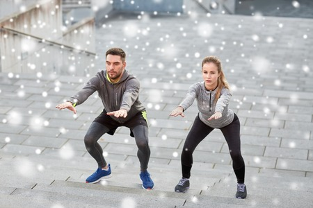 fitness, sport, exercising, people and healthy lifestyle concept - man and woman doing squats outdoors over snow