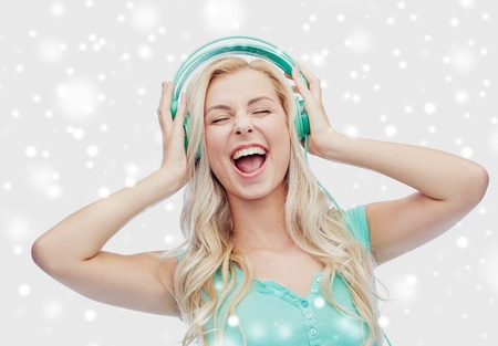 music, technology, winter holidays, christmas and people concept - happy young woman or teenage girl with headphones singing song over snow Stock Photo