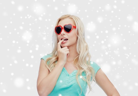 valentines day, winter holidays, christmas and people concept - smiling young woman or teenage girl in heart shaped sunglasses over snow Stock Photo
