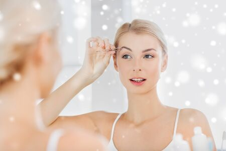 tweezing: beauty and people concept - smiling young woman with tweezers tweezing eyebrow and looking to mirror at home bathroom over snow
