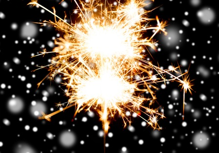 christmas, holidays, new year party and pyrotechnics concept - sparkler or bengal light burning over black background with snow Stock Photo