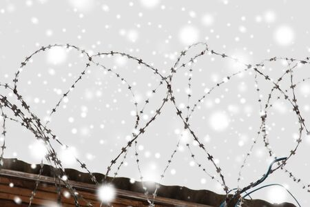 martial law: imprisonment and restriction concept - barb wire fence over gray sky and snow