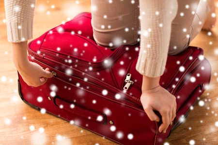baggage: vacation, travel, tourism, winter holidays and objects concept - close up of woman packing and zipping bag Stock Photo