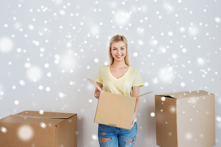 nice accommodations: moving, delivery, housing, accommodation and people concept - smiling young woman with cardboard box at home over snow