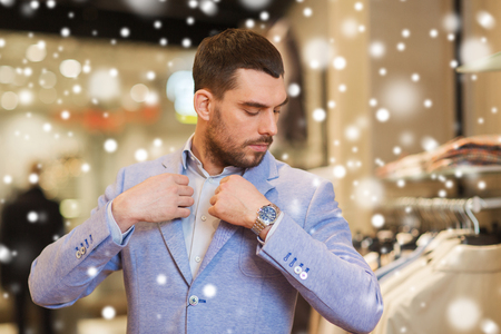 lifestyle shopping: sale, shopping, fashion, style and people concept - elegant young man choosing and trying jacket on in mall or clothing store over snow Stock Photo