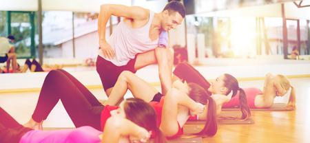 mujeres juntas: fitness, deporte, entrenamiento, gimnasio y el concepto de estilo de vida - grupo de mujeres sonrientes con el entrenador masculino haciendo abdominales sobre esteras en el gimnasio