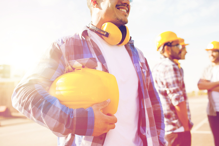 safety gear: building, protective gear and people concept - close up of builder holding yellow hardhat or helmet at construction site