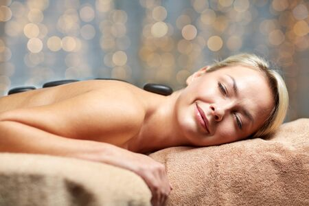 masajes relajacion: people, beauty, spa, healthy lifestyle and relaxation concept - close up of beautiful young woman having hot stone massage in spa Foto de archivo