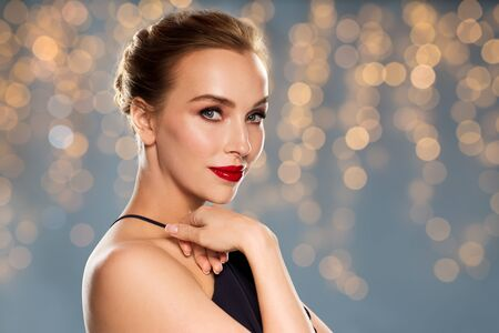 femme fatale: people, luxury and fashion concept - beautiful woman in black with red lips over holidays lights background