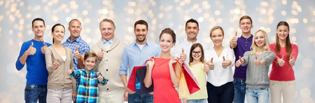 three generations of women: sale, family, generation and people concept - group of happy men and women with shopping bags showing thumbs up over holidays lights background Stock Photo