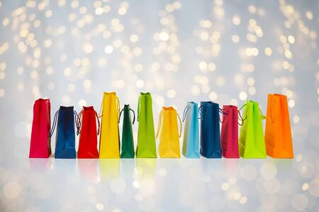 overspending: sale, consumerism and retail concept - many colorful shopping bags over holidays lights background