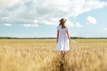 campo de flores: la felicidad, la naturaleza, las vacaciones de verano, vacaciones y la gente concepto - mujer joven y sonriente en la guirnalda de flores y el vestido blanco caminando a lo largo de campo de cereales
