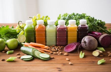 una sana alimentazione, bevande, dieta e il concetto di disintossicazione - bottiglie di plastica con diversi succhi di frutta o di verdura e cibo sul tavolo in legno Archivio Fotografico