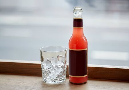 aperitive: drinks concept - bottle of lemonade and glass with ice on cafe table