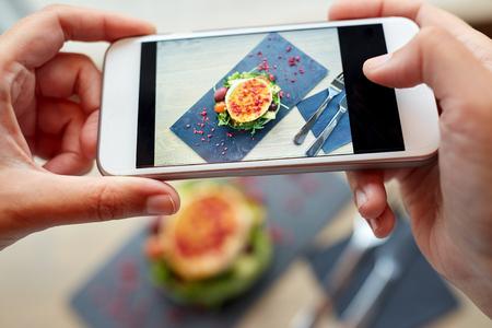 tomando refresco: alimentos, culinario, tecnología y personas concepto - manos de la mujer con ensalada de queso de cabra teléfono inteligente fotografiar con los vehículos y las frambuesas secas en el restaurante o cafetería Foto de archivo