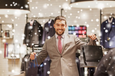 retail store: sale, fashion, retail, business style and people concept - happy man with shopping bags at clothing store over snow