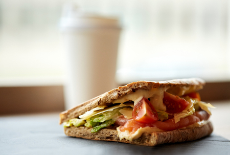 food, dinner and eating concept - salmon panini sandwich with tomatoes and cheese on stone plate at cafe
